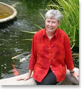 Maria Klawe sitting next to a Koi pond